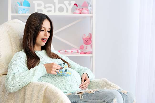 Pregnant woman sitting in armchair, indoors