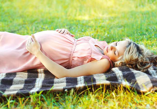 Pregnant woman lying resting on grass in summer day